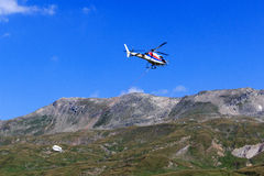 Vervoerhelikopter die met levering en bergpanorama vliegen, de Alpen van Hohe Tauern, Oostenrijk Royalty-vrije Stock Fotografie