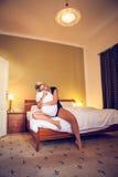 Vervollkommnen Sie junge Dame in der Liebe, die auf dem Bett und den Spielen mit einem Kissen sitzt Stockfotografie