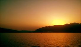 Vervollkommnen Sie orange Sonnenuntergang, adriatisches Meer und Berge Stockfoto