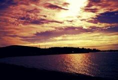 Vervollkommnen Sie orange Sonnenuntergang, Himmel mit Wolken, adriatisches Meer, Strand und Hafenbar Lizenzfreie Stockfotos