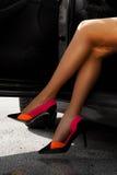Vervollkommnen Sie weibliche Beine in den Strumpfhosen und in den hohen Absätzen im Auto Stockfoto
