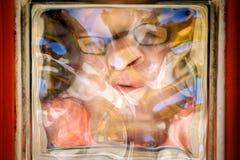 Vervormd Meisjesgezicht door Glasblok stock fotografie