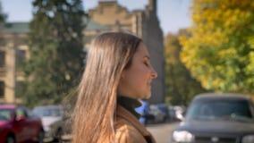 Vervuilend in motie, glimlacht het Kaukasische wijfje bij camera gelukkig en dat die recht terwijl het gaan op de straat kijken stock video