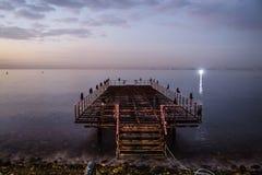 Verwüstetes Dock auf Sonnenuntergang mit ruhigem See stockbild