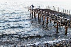 Verwüstetes Dock auf Sonnenuntergang mit ruhigem See stockfoto