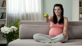 Verwachtende mum die groene appel, tribunes voor gezonde levensstijl, het geven tonen van kind royalty-vrije stock afbeeldingen