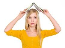 Verward studentenmeisje met opgeheven boekoverheadkosten Stock Foto