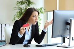 Verwarde beambte die online met creditcard proberen te betalen stock fotografie