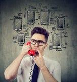 Verwarde bedrijfsmens die over verschillende apparaten denken stock fotografie