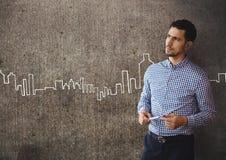 Verwarde bedrijfsmens die zich tegen grijze muurachtergrond bevinden met stadspictogrammen Royalty-vrije Stock Afbeelding