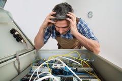 Verwarde elektricien die zekeringkast bekijken Stock Foto's