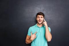 Verwarde jonge mens die op celtelefoon spreken over witte achtergrond Stock Foto's