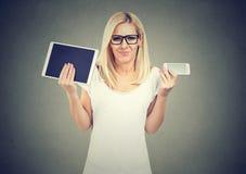 Verwarde jonge vrouw die in glazen onzekere schouders ophalen wat om tablet of smartphone te kiezen Stock Afbeelding