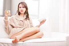 Verwarde jonge vrouw met thee en tablet Stock Fotografie