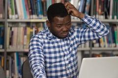 Verwarde Mannelijke Student Reading Many Books voor Examen Stock Afbeelding