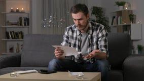 Verwarde mens die een brief thuis lezen stock video