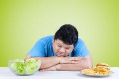 Verwarde mens met salade en hamburger Royalty-vrije Stock Afbeeldingen