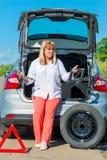 Verwarde rijpe vrouwenbestuurder dichtbij zijn auto Stock Afbeelding