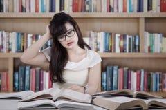 Verwarde student die vele boeken 1 lezen Royalty-vrije Stock Foto's