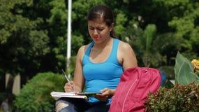 Verwarde Student Writing Beautiful Female stock fotografie