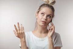 Verwarde in verwarring gebrachte vrouw die haar slimme telefoon houden Menselijke emoties, kinetisch gedrag royalty-vrije stock afbeeldingen