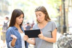 Verwarde vrienden die online inhoud in een tablet lezen royalty-vrije stock afbeelding