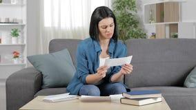 Verwarde vrouw die een ontvangstbewijs thuis lezen stock footage