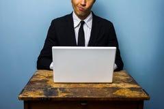 Verwarde zakenman die aan laptop werken Stock Foto's