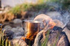 Verwarmende kop thee op open brand bij het wilde kamperen stock afbeelding
