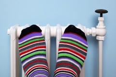 Verwarmende voeten op de radiator Stock Afbeelding