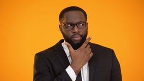 In verwarring gebrachte Afro-Amerikaanse zakenman die opties, ontoereikende informatie overwegen stock video