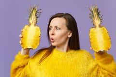In verwarring gebrachte jonge vrouw die in de greep van de bontsweater in handen op halfs van vers rijp ananasfruit kijken op vio royalty-vrije stock afbeelding