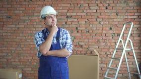 In verwarring gebrachte mens in een werkende eenvormige en witte helm tegen een bakstenen muur stock videobeelden