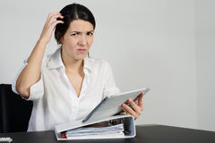 In verwarring gebrachte vrouw die haar hoofd krassen Stock Foto