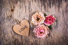 Verwelkte Rosen und ein hölzernes Herz Geführte Liebe Verwelkte Blumen auf einem alten hölzernen Hintergrund Lizenzfreie Stockfotos