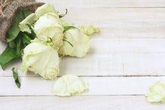 Verwelkter Blumenstrauß von den weißen Rosen eingewickelt in der Leinwand Lizenzfreies Stockfoto