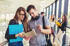 Verwendende Studenten sie digitale Tablette in einer Universit?t lizenzfreie stockfotografie