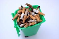 Verwendete Zigarettenkippen im Gartenabfällebehälter auf weißem Hintergrund Stockfoto