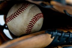 Verwendeter Baseball innerhalb eines Handschuhs stockfotos