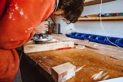Verwerking van een meubilairdeel door een machine om een boom op te poetsen de malende machine op een raad, selectieve nadruk Royalty-vrije Stock Fotografie