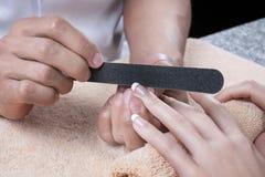 Verwerking van spijkers door een nagelvijl Stock Foto