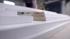Verwerkte randen van houten die spaanplaat op een lijst in een workshop, close-upmening in beweging worden gestapeld stock footage