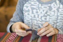 verwezenlijking het meisje naait stuk speelgoed dat van gevoeld wordt gemaakt Het meisje naait een grijze muis Het meisje naait e stock foto