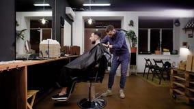 Verwezenlijking van modieus kapsel in kapperswinkel Kapper en mannelijke klant Mening van binnenland stock video