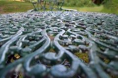 Verwickelt verzierte Roheisentischplatte in einem Garten stockbild