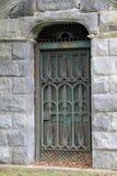 Verwickeltes Detail in der Metalltür und alte Steinstruktur am Friedhof Stockbild