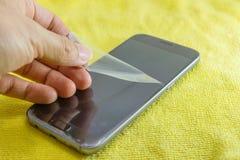 Verwijder het oude slimme telefoonscherm beschermen Stock Foto's