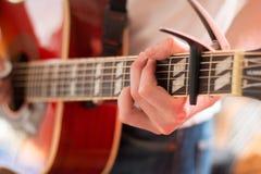 Verwijderd van een jonge mens die een zonnestraal westelijke gitaar spelen stock foto's