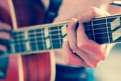 Verwijderd van een jonge mens die een zonnestraal westelijke gitaar spelen royalty-vrije stock foto's