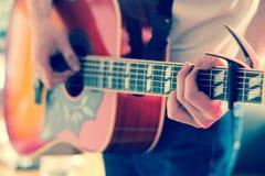 Verwijderd van een jonge mens die een zonnestraal westelijke gitaar spelen stock afbeelding